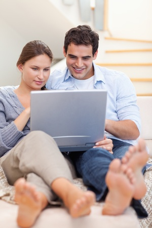Portrait of a couple using a laptop while lying on a couch in their living room Stock Photo - 11632633