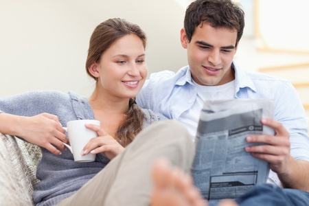 news room: Couple reading the news while lying on a sofa looking away from the camera