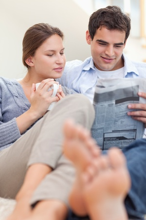 Couple reading a newspaper while lying on a sofa looking away from the camera photo