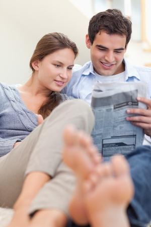 Portrait of a couple reading a newspaper while lying on a couch in their living room photo