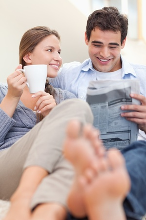 Portrait of a smiling couple reading a newspaper in the morning in their living room photo