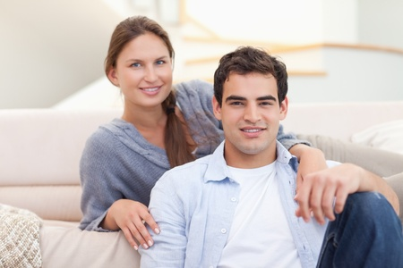 Couple sitting in their living room while looking at the camera photo