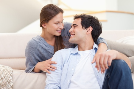 Young couple sitting in their living room while looking at each other photo