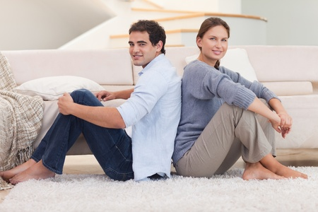 Young couple sitting back to back in their living room photo
