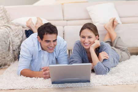 Couple watching a movie with a laptop while lying on a carpet photo