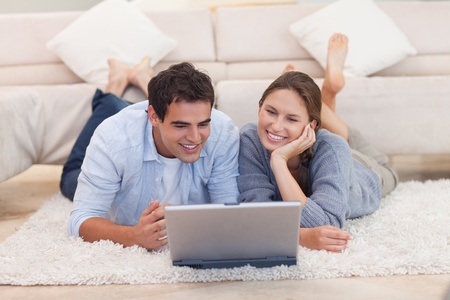 Young couple looking for something on the internet while lying on a carpet photo