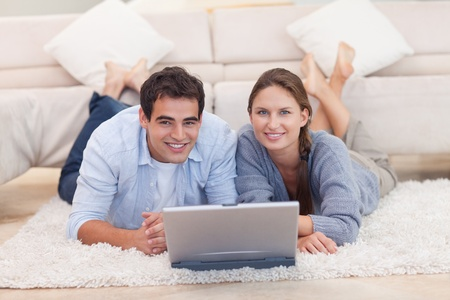 Cute couple posing with a laptop while lying on a carpet Stock Photo - 11632649