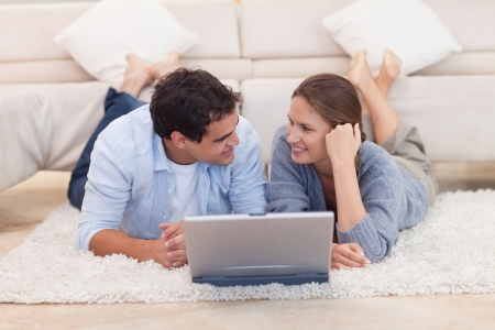 Couple posing with a laptop while looking at each other photo