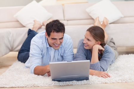 Smiling couple surfing on the internet while lying on a carpet photo