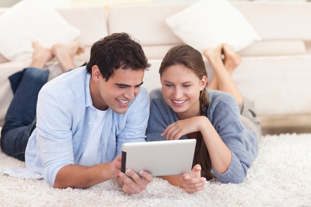 Smiling couple using a tablet computer while lying on a carpet photo