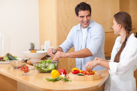 Smiling couple preparing a salad in their kitchen photo