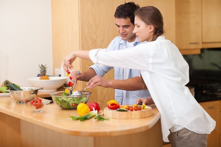 vegetables young couple: Happy couple preparing a salad in their kitchen Stock Photo