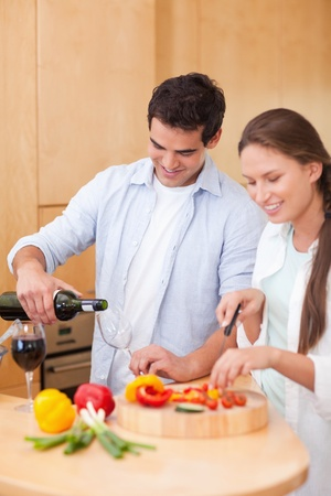 Portrait of a young man pouring a glass of wine while his wife is cooking in their kitchen photo