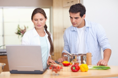 Couple using a laptop to cook in their kitchen photo