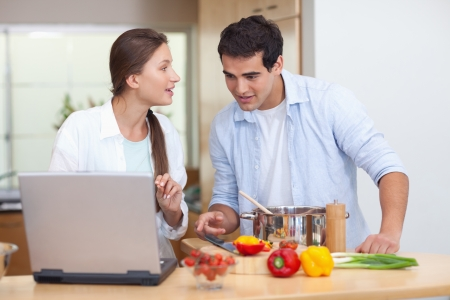 Couple using a notebook to cook in their kitchen photo