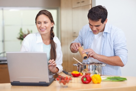 Young couple using a notebook to cook in their kitchen photo