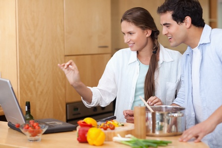 Smiling couple using a laptop to cook in their kitchen photo