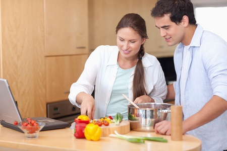 Happy couple using a laptop to cook in their kitchen photo