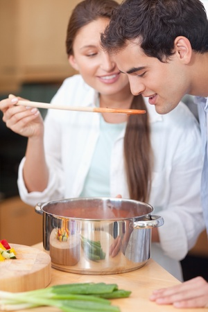 vegetables young couple: Portrait of a man trying his wifes sauce in their kitchen
