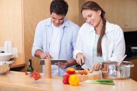 Couple using a tablet computer to cook in their kitchen photo