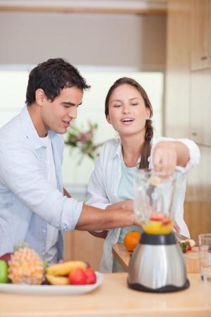 licuadora: Retrato de una pareja haciendo el jugo de fruta fresca en su cocina