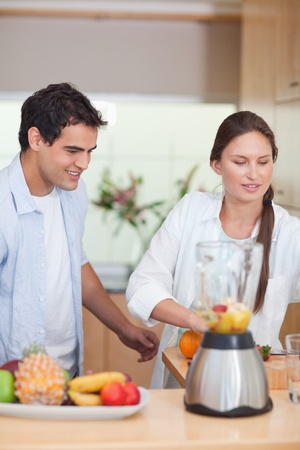 Portrait of a young couple making fresh fruits juice in their kitchen photo