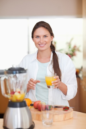 Portrait of a woman drinking fresh fruits juice in her kitchen Stock Photo - 11632229