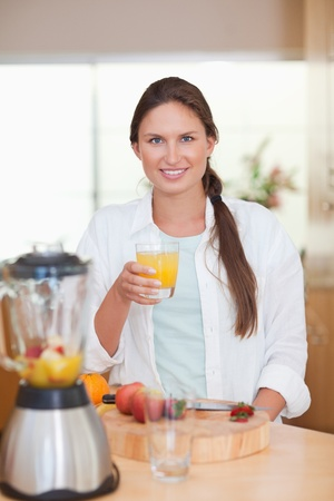 Portrait of a young woman drinking fresh fruits juice in her kitchen Stock Photo - 11632240