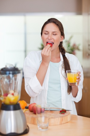 Portrait of a cute woman eating a fresh strawberry in her kitchen Stock Photo - 11632421