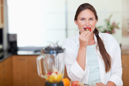 Woman eating a strawberry in her kitchen photo