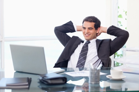 Relaxed businessman working with a laptop in his office photo