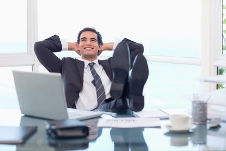 relaxed business man: Satisfied businessman relaxing in his office