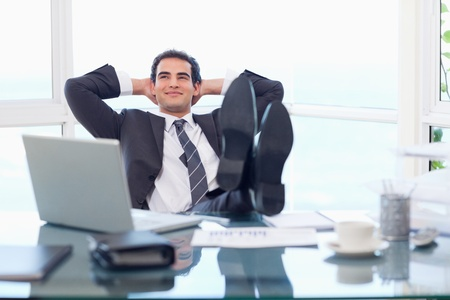 Smiling businessman relaxing in his office photo