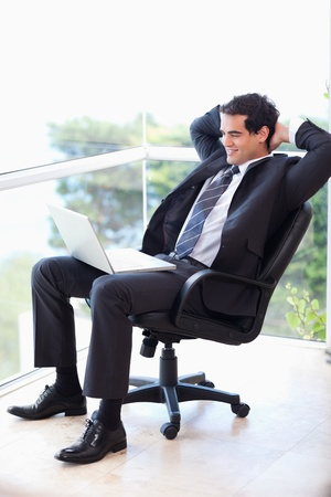 Portrait of a relaxed businessman sitting on an armchair working with a laptop in his office photo