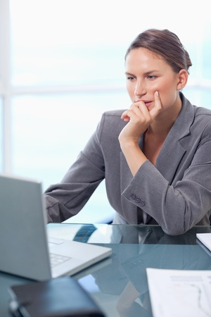 Portrait of a thoughtful businesswoman working with a laptop in her office photo
