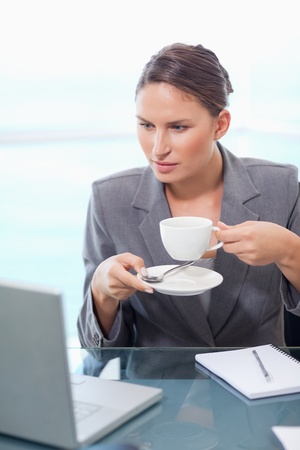 Portrait of a businesswoman drinking coffee in her office photo
