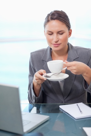 Portrait of a businesswoman drinking tea in her office Stock Photo - 11632223