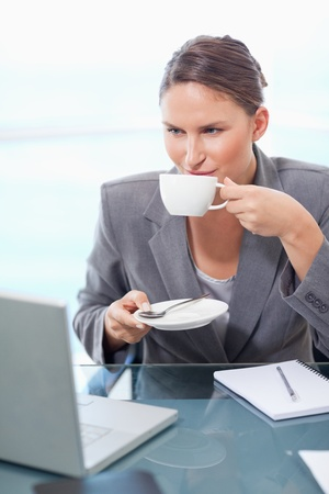 Portrait of a young businesswoman drinking tea in her office photo