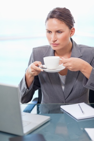 Portrait of a serious businesswoman drinking tea in her office photo