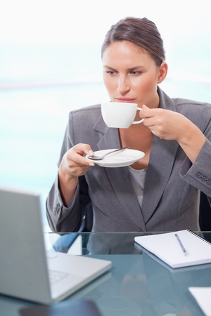 Portrait of a serious businesswoman drinking coffee in her office photo