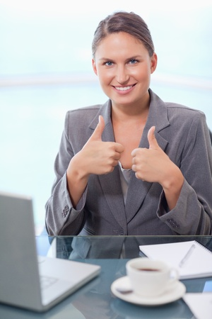 Portrait of a businesswoman with the thumbs up in her office photo