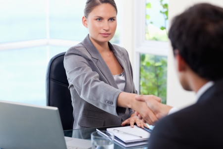 Young businesswoman shaking hands with customer photo