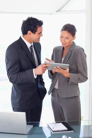 Young business partner looking at tablet in their hands photo