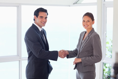 Side view of smiling young trade partner shaking hands photo