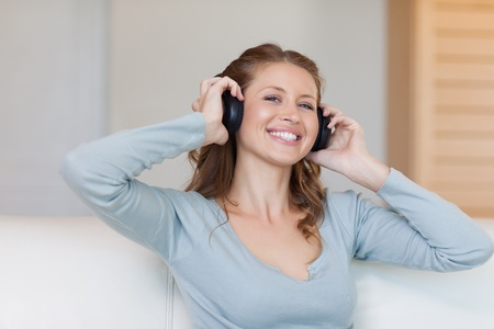 Smiling young woman with headphones on the sofa photo