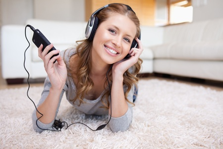 Young woman lying on the floor enjoying music Stock Photo - 11716612