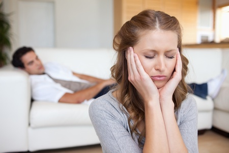 Young woman having headache white man lying on sofa behind her photo