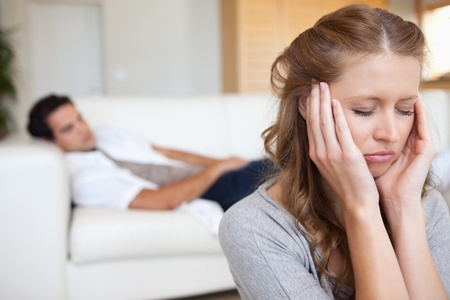 difficulties: Young woman experiencing headache with man on the sofa behind her Stock Photo
