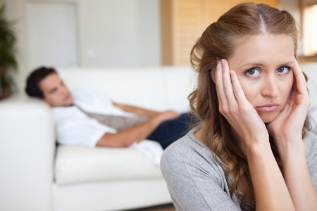 Young woman suffering from headache with man on the sofa behind her photo