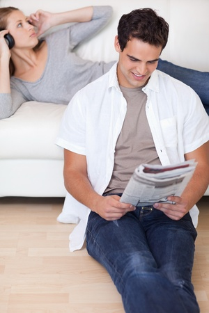 Young man reading the news while his girlfriend is listening to music on the sofa photo